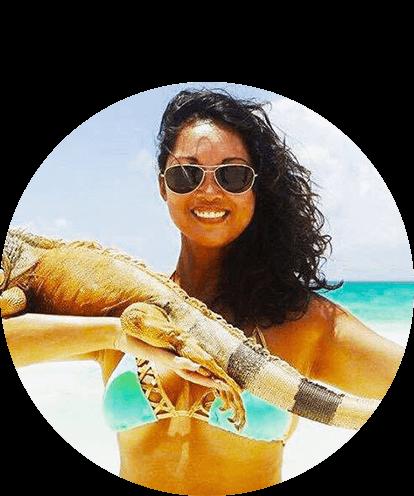 Maria Remington at beach with iguana on arm.