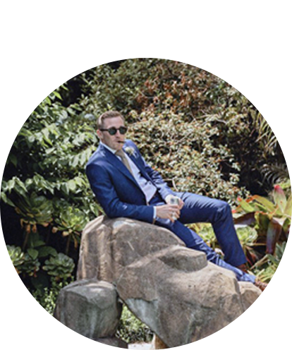 Clark Hennessy sitting on a rock with pen in mouth and wearing a suit.