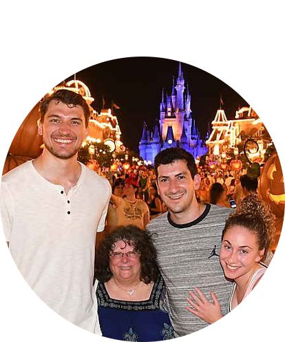 Cory Dolins with two women and one man posing with Disney Magic Kingdom castle in background.
