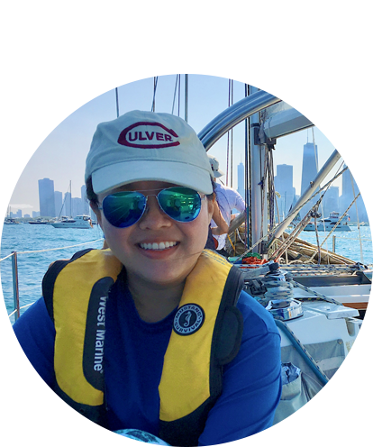 Annie Wang sitting on deck of sailboat with Chicago daytime skyline in background.