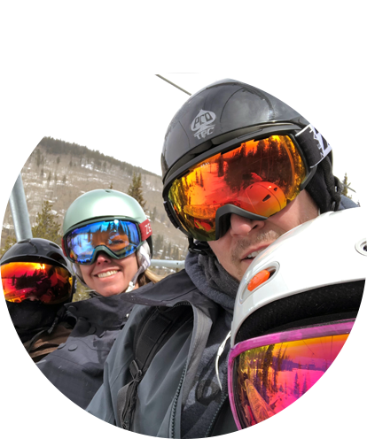 Julie Bewley on chairlift seated with family in ski googles and safety helmets.