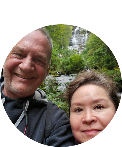 Rick Berkimer with female posing in front of a forested waterfall area.