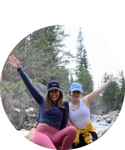 Vanessa Contreras fun photo with female friend waiving from a riverbed in woods/forest.