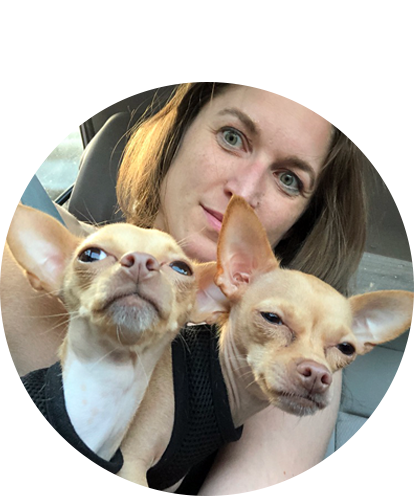 Heather McCabe fun photo holding two small dogs in her lap seating in automobile.